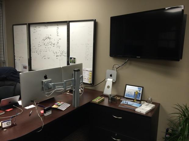Televisor de pared con Mac Mini junto a pantallas de iluminación